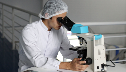 A Male Scientist in a White Lab Coat Looking Into a Microscope